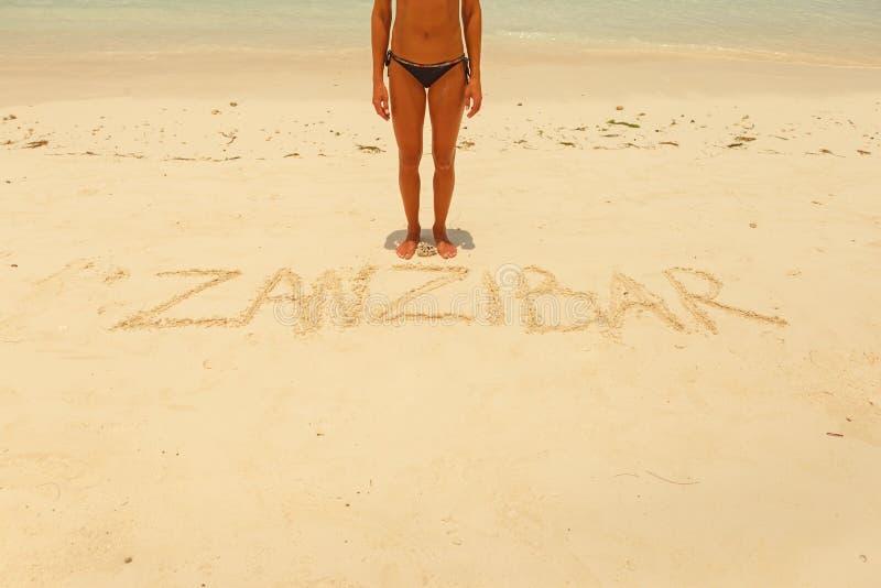 Posição da jovem mulher perto da areia zanzibar da inscrição imagem de stock