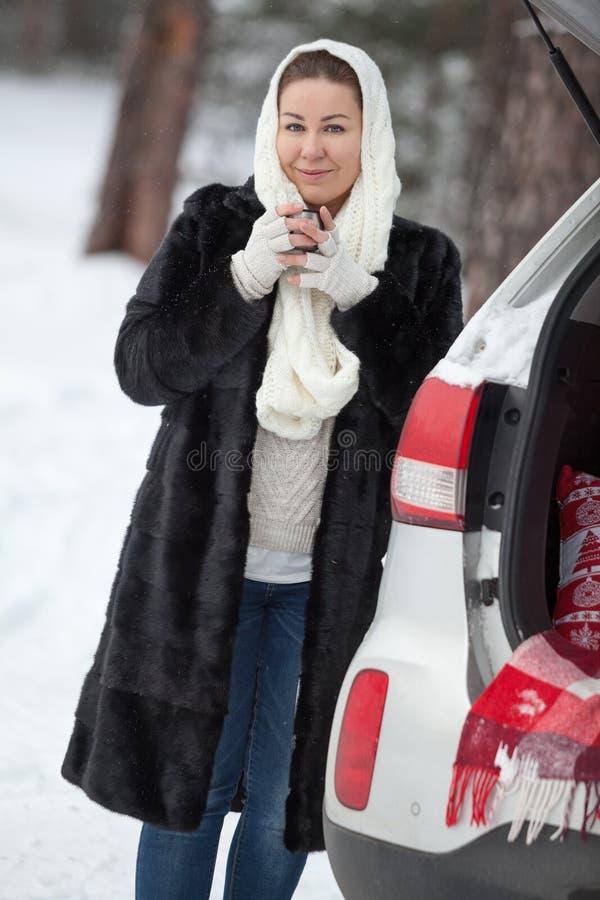 Posição da jovem mulher perto do suv e guardar a caneca do chá nas mãos na estação do inverno fotografia de stock royalty free