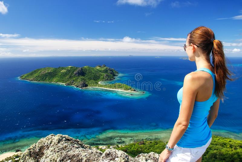 Posição da jovem mulher sobre o vulcão de Vatuvula com uma vista da ilha de Kuata, ilha de Wayaseva, Yasawas, Fiji fotografia de stock