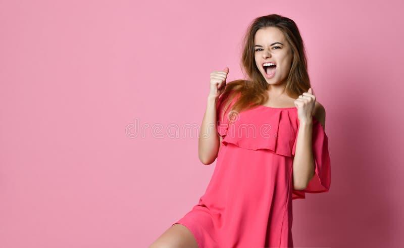 A posição da jovem senhora isolada sobre o fundo cor-de-rosa faz o gesto do vencedor foto de stock