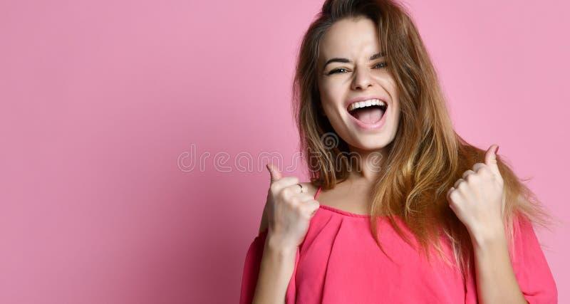 A posição da jovem senhora isolada sobre o fundo cor-de-rosa faz o gesto do vencedor foto de stock royalty free
