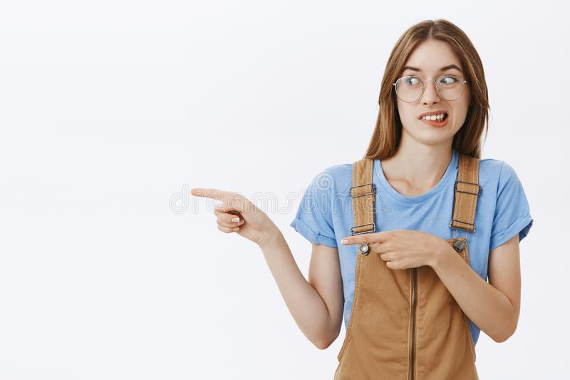Posição da menina com o esquisito assustador da exibição do indivíduo ao amigo Fêmea europeia encantador desagradada intensa em b fotografia de stock royalty free