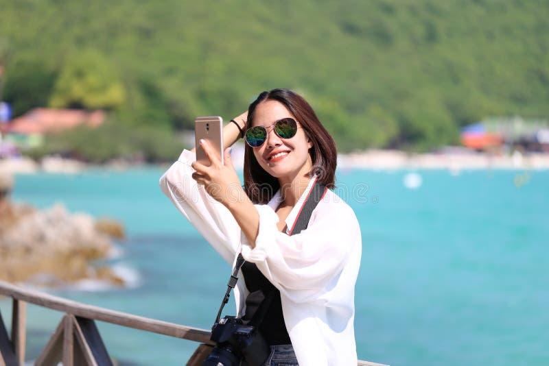 Posição da moça do moderno na ponte e selfie da tomada com a praia tropical do smartphone das montanhas fundo, Koh Larn imagens de stock