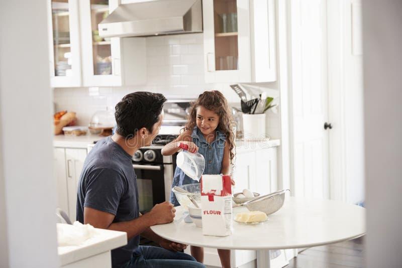 Posição da moça na mesa de cozinha que prepara a mistura do bolo com seu pai, visto da entrada imagem de stock royalty free
