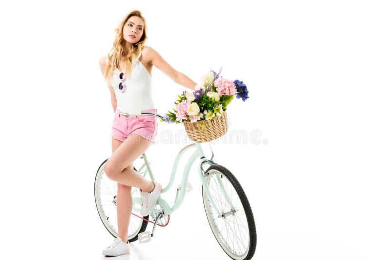 Posição da moça pela bicicleta do cruzador com as flores na cesta fotos de stock