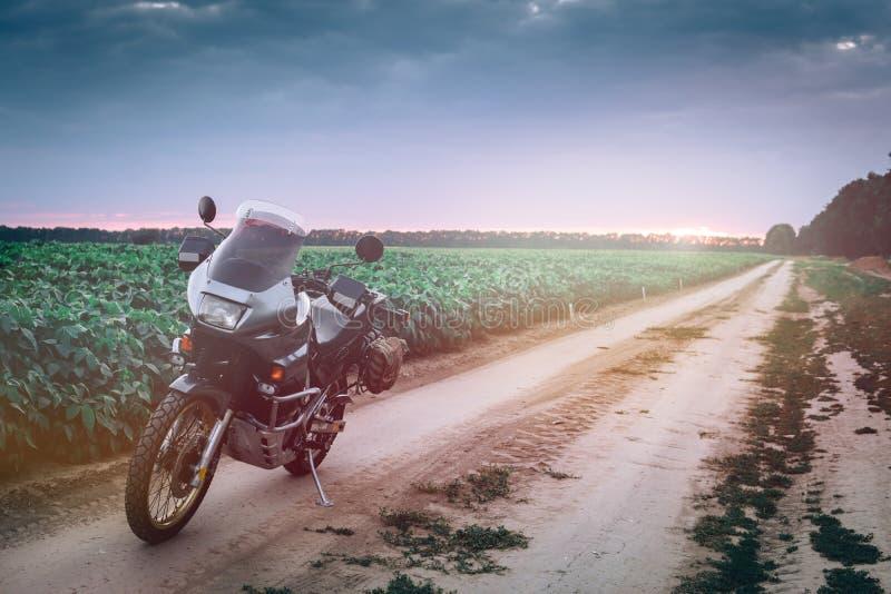 Posição da motocicleta da aventura em uma estrada de terra no suset, fora do conceito do curso da estrada, equipamento do caval fotos de stock royalty free