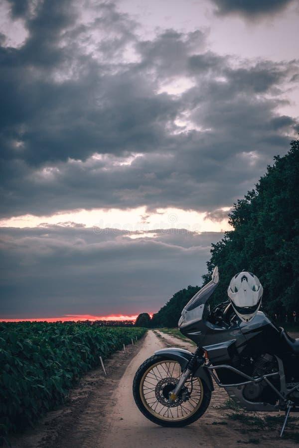 Posição da motocicleta da aventura em uma estrada de terra no suset, fora do conceito do curso da estrada, equipamento do caval imagem de stock royalty free