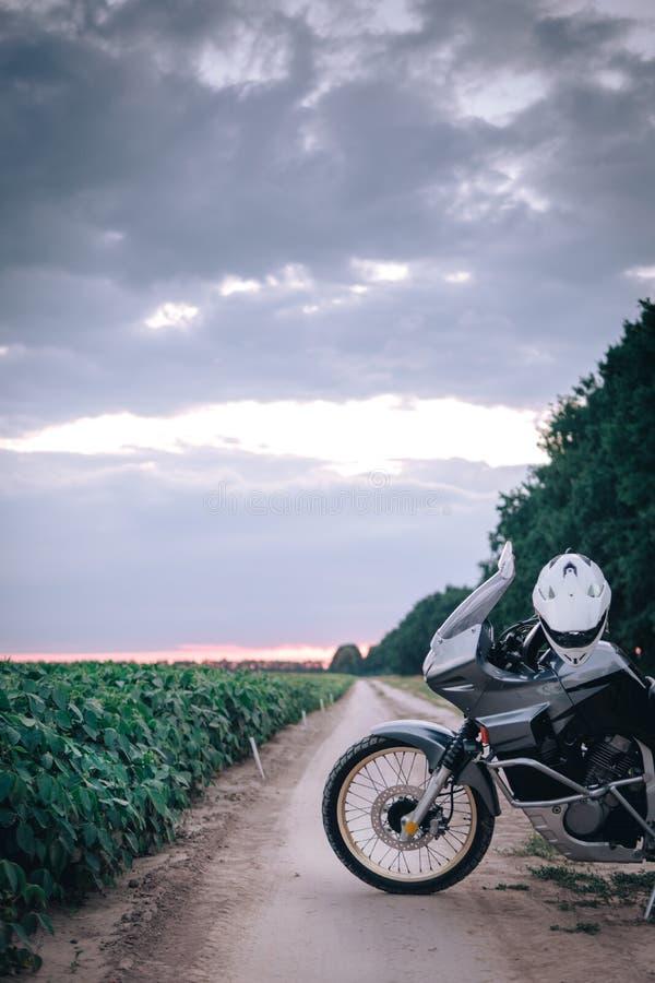 Posição da motocicleta da aventura em uma estrada de terra no suset, fora do conceito do curso da estrada, equipamento do caval imagem de stock
