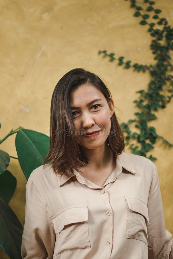 Posição da mulher com parede amarela fotografia de stock