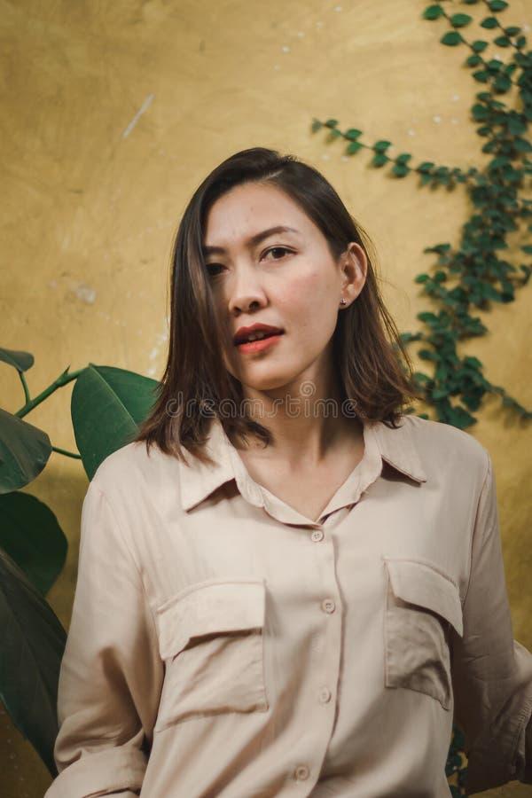 Posição da mulher com parede amarela imagem de stock royalty free