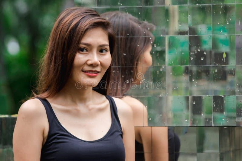 Posição da mulher contra uma parede com um espelho fotografia de stock royalty free