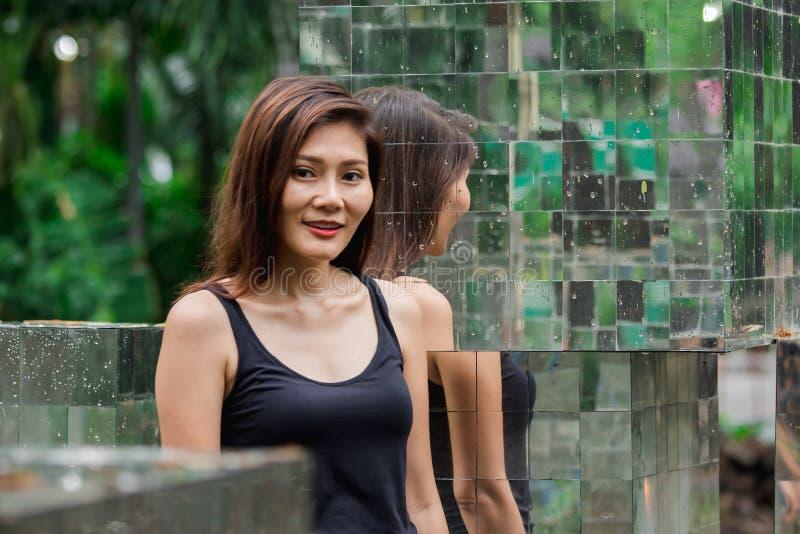 Posição da mulher contra uma parede com um espelho imagem de stock royalty free