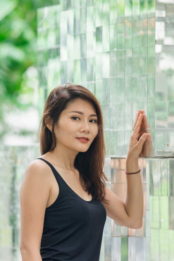 Posição da mulher contra uma parede com um espelho fotos de stock