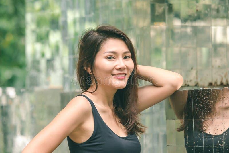 Posição da mulher contra uma parede com um espelho foto de stock
