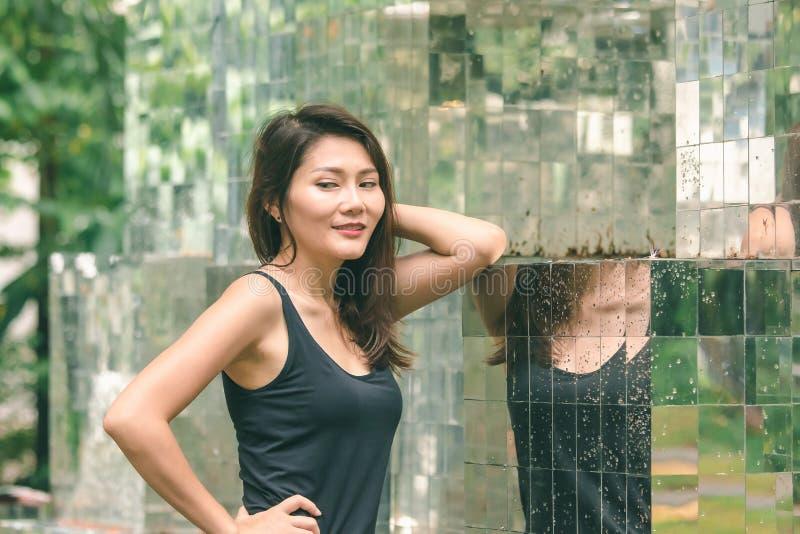 Posição da mulher contra uma parede com um espelho fotos de stock royalty free