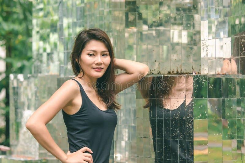 Posição da mulher contra uma parede com um espelho imagens de stock