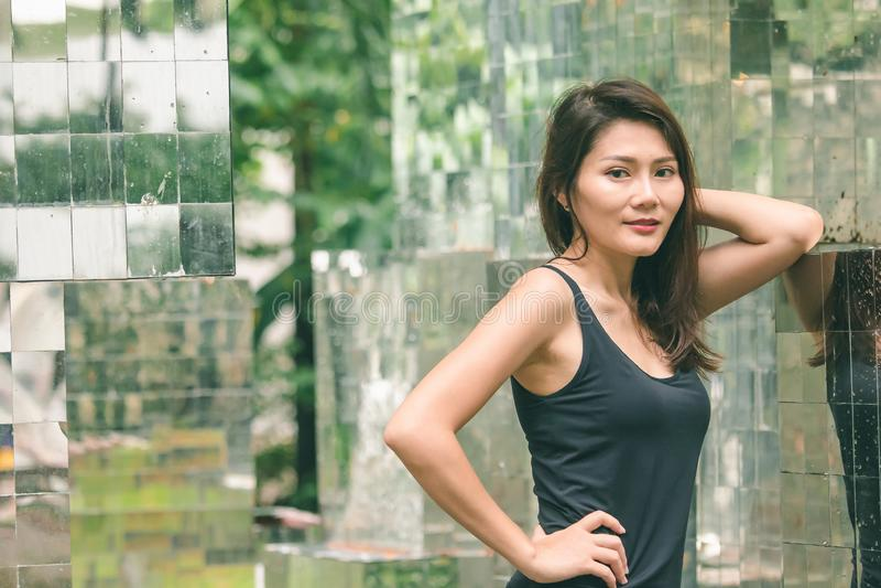 Posição da mulher contra uma parede com um espelho imagens de stock royalty free