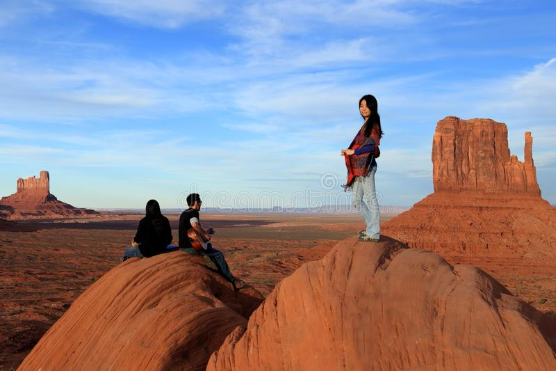 Posição da mulher do Navajo e dois músicos do Navajo que sentam-se jogando a música em rochas imagens de stock