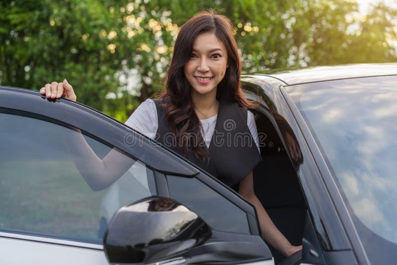 A posição da mulher e abre a porta de carro imagens de stock royalty free