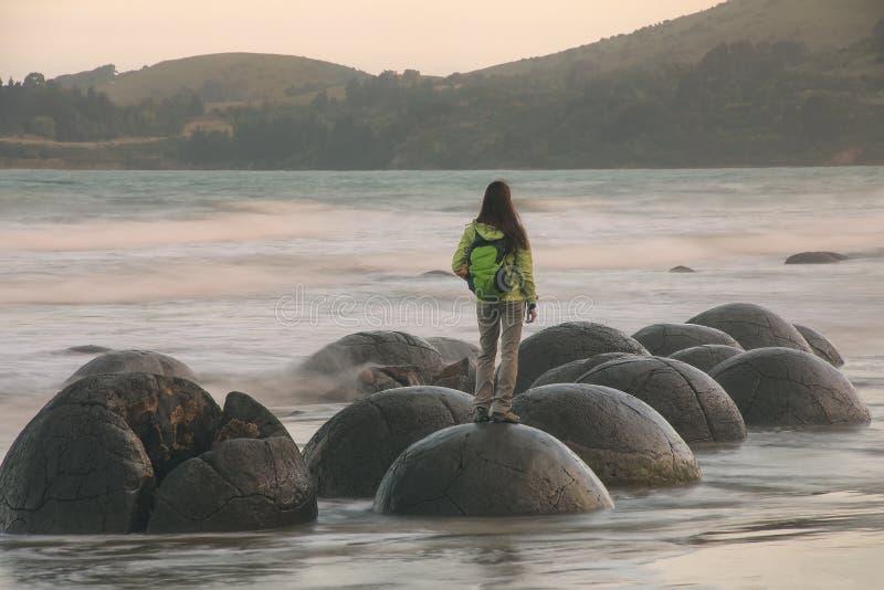Posição da mulher em Moeraki Boulder na praia de Koekohe, Otago, ilha sul, Nova Zelândia fotos de stock