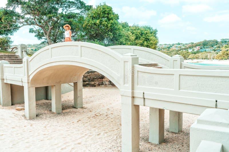 Posi??o da mulher na ponte arqueada na praia do Balmoral foto de stock royalty free