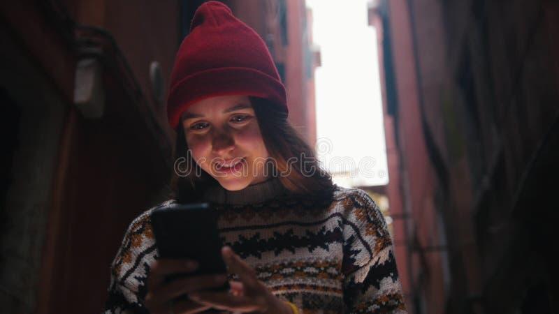 Posição da mulher nas escadas entre as construções e a vista de seu telefone imagens de stock royalty free