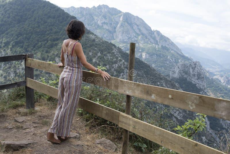 Posição da mulher nela que inclina-se para trás em trilhos de madeira na paisagem asturiana bonita foto de stock