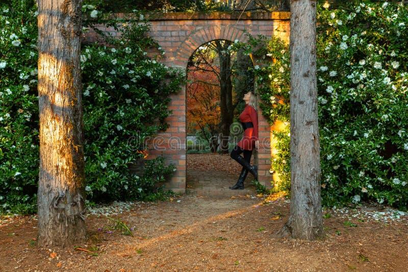 Posição da mulher no arco de pedra bonito do jardim imagens de stock royalty free