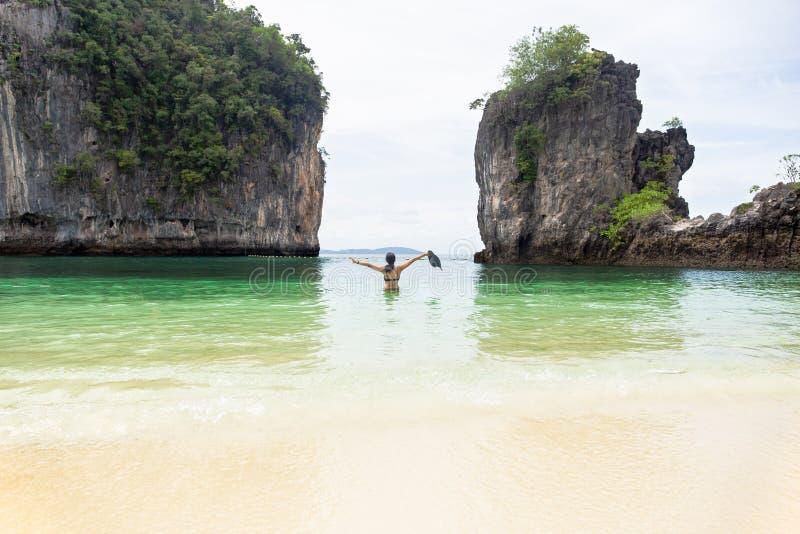 Posição da mulher no mar e mãos acima de guardar o chapéu da praia em férias imagem de stock royalty free