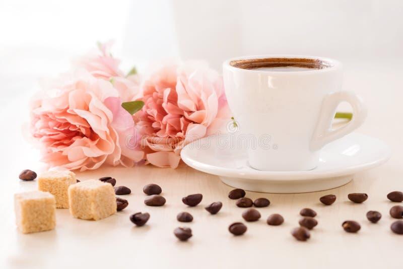 Posição da xícara de café na tabela com os feijões de café dispersados ao redor e as partes de açúcar de bastão, foto de stock royalty free