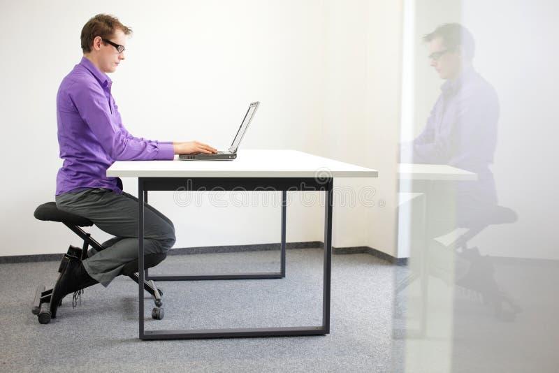 posição de assento correta na estação de trabalho. homem na cadeira do ajoelhamento foto de stock royalty free