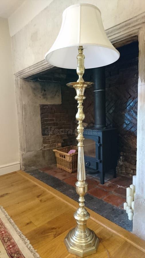Posição de bronze da lâmpada de assoalho em um aparador imagens de stock royalty free