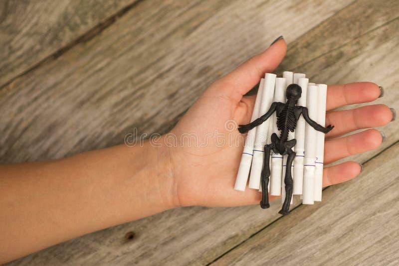 A posição de esqueleto preta em muitos cigarros na mão do fumador, fumando mata o conceito imagem de stock