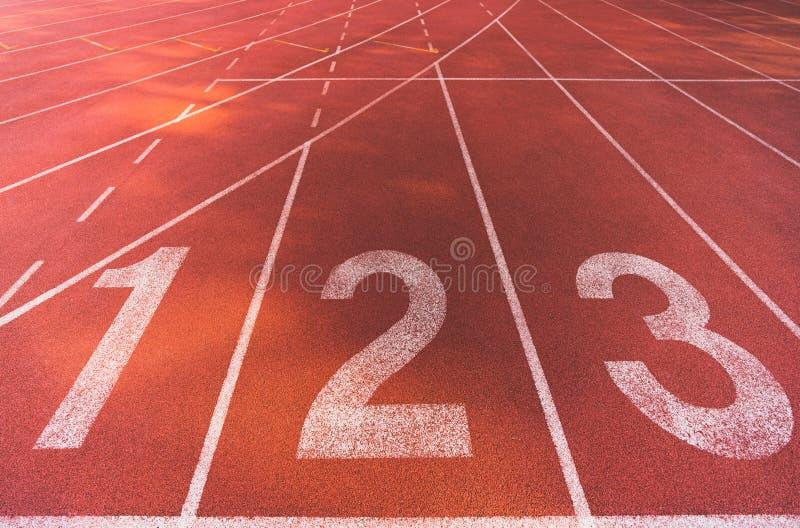 Posição de linha de partida da textura do fundo da pista de atletismo, pista número 1, 2, 3 Concorrência do negócio conceptual fotos de stock royalty free