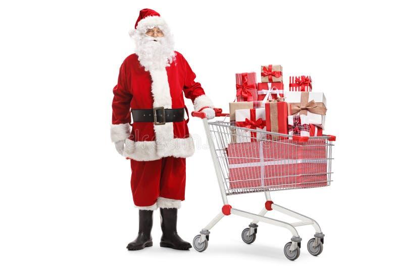 Posição de Papai Noel com presentes em um carrinho de compras imagens de stock