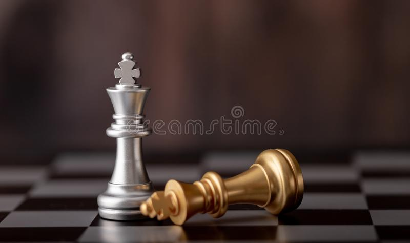 posição de prata e ouro do rei que caem na placa de xadrez imagem de stock