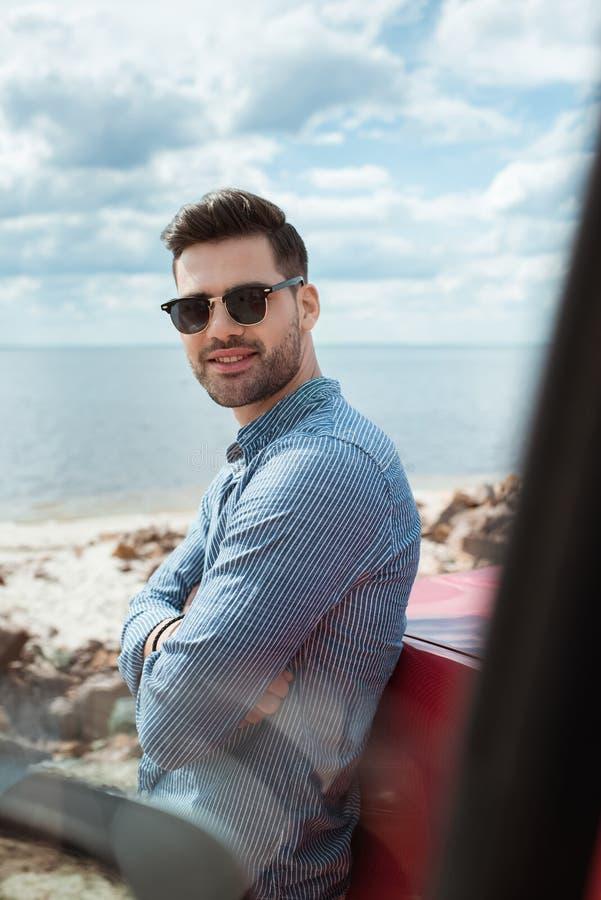 posição de sorriso considerável do homem no carro perto do mar durante foto de stock royalty free