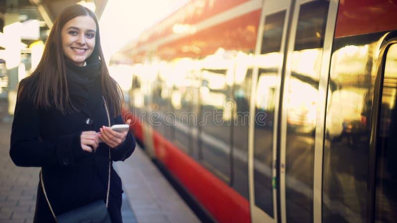Posição de sorriso da senhora no estação de caminhos de ferro e em bilhetes de registro em linha no smartphone fotografia de stock