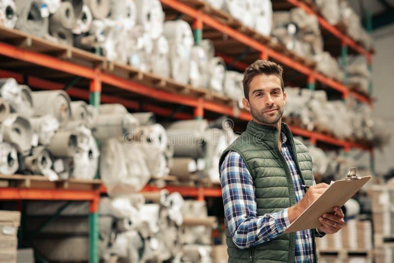 Posição de sorriso do trabalhador em um assoalho do armazém que faz o inventário imagens de stock