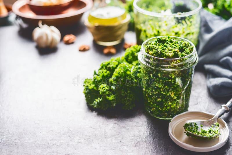 Posição de vidro do pesto caseiro verde da couve no fundo rústico escuro com ingredientes, vista superior da mesa de cozinha Prep imagem de stock royalty free