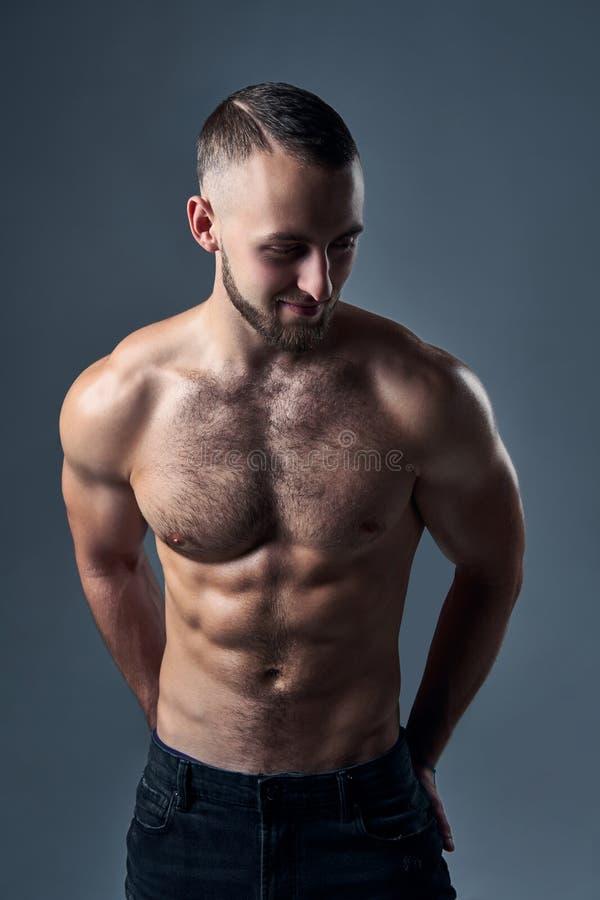 Posição descamisado muscular do homem com mãos em uns bolsos fotografia de stock