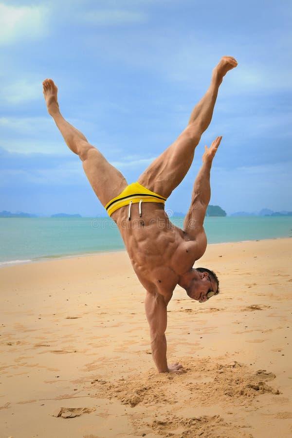 Posição despida nova muscular do indivíduo nas mãos na praia fotografia de stock royalty free