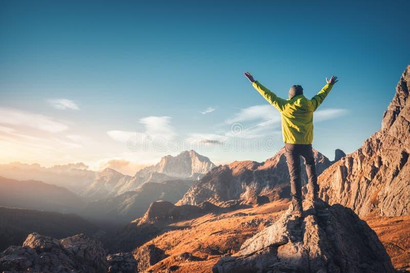 Posição desportiva do homem na pedra com os braços acima aumentados foto de stock royalty free