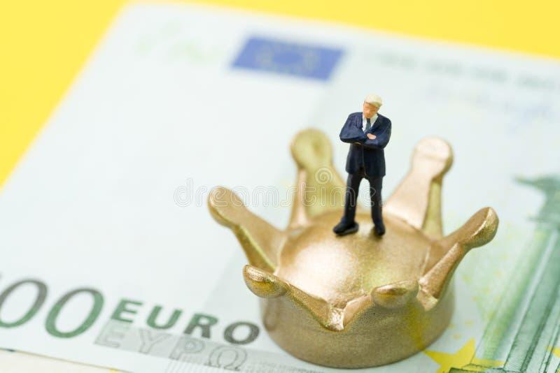 Posição diminuta do homem de negócios na coroa dourada no dinheiro das cédulas do Euro usando-se como o rei ou o vencedor da econ fotografia de stock royalty free