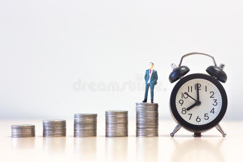 Posição diminuta na pilha da moeda do dinheiro com despertador, conceito do homem de negócios dos povos do desenvolvimento susten fotos de stock royalty free