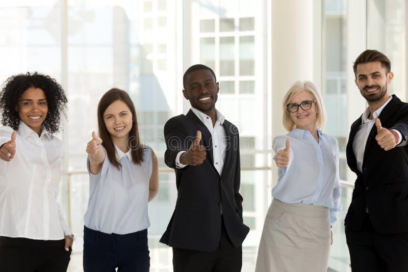 Posição diversa feliz dos empresários que olha a câmera que mostra os polegares acima imagens de stock royalty free