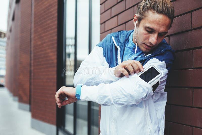 A posição do atleta na rua perto da parede de tijolo e do telefone celular da verificação, prepara-se para começar a correr a ses fotografia de stock
