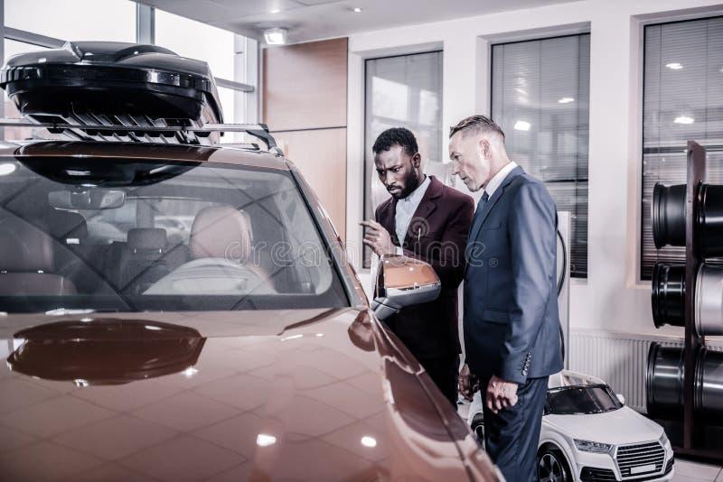 Posição do consultante perto do automóvel de passageiros grande com seu cliente fotos de stock royalty free