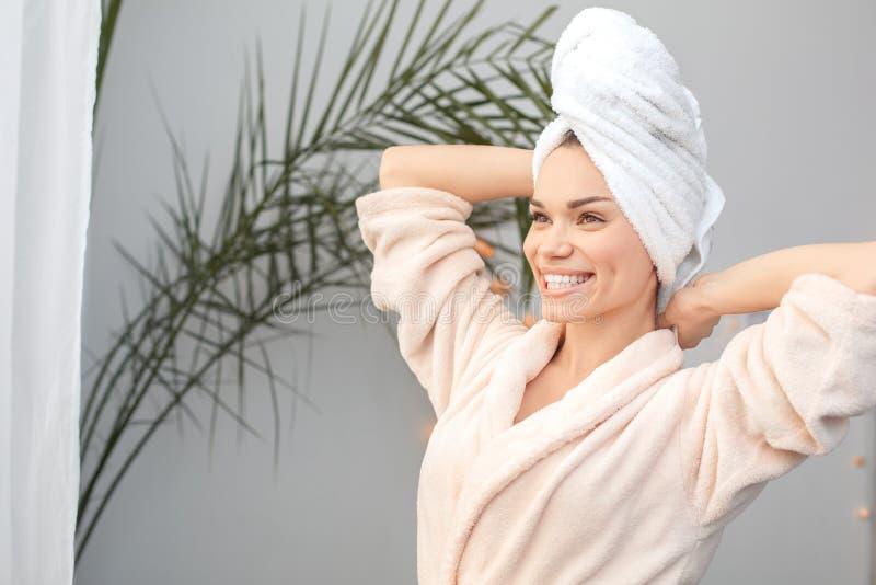 Posição do cuidado da beleza da jovem mulher em casa na toalha que estica olhando para fora a janela alegre fotos de stock