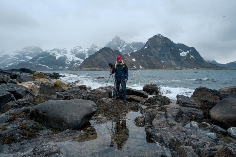 Posição do fotógrafo do homem novo na rocha nas montanhas na praia que fotografa as paisagens em ilhas de Lofoten dentro fotografia de stock royalty free
